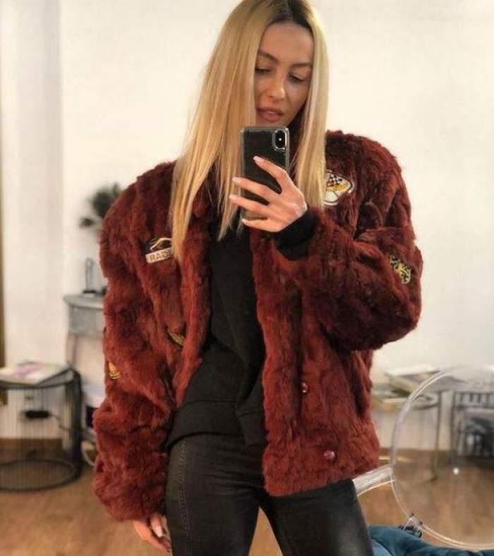 Flavia Mihășan poartă haină de blană maro și pantaloni negri. Vedeta își face o poză în oglindă cu telefonul mobil și stă în picioare.