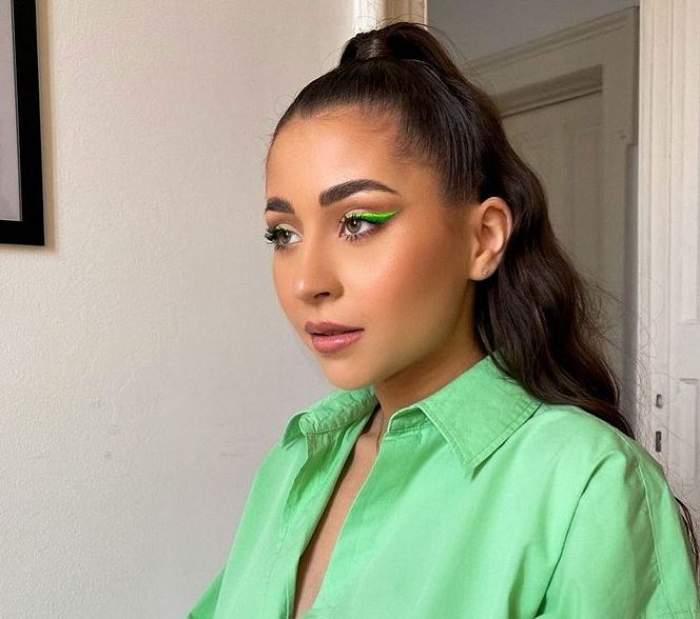 Nicole Cherry poartă o cămașă verde, are părul prins în coadă și ține gura întredeschisă.