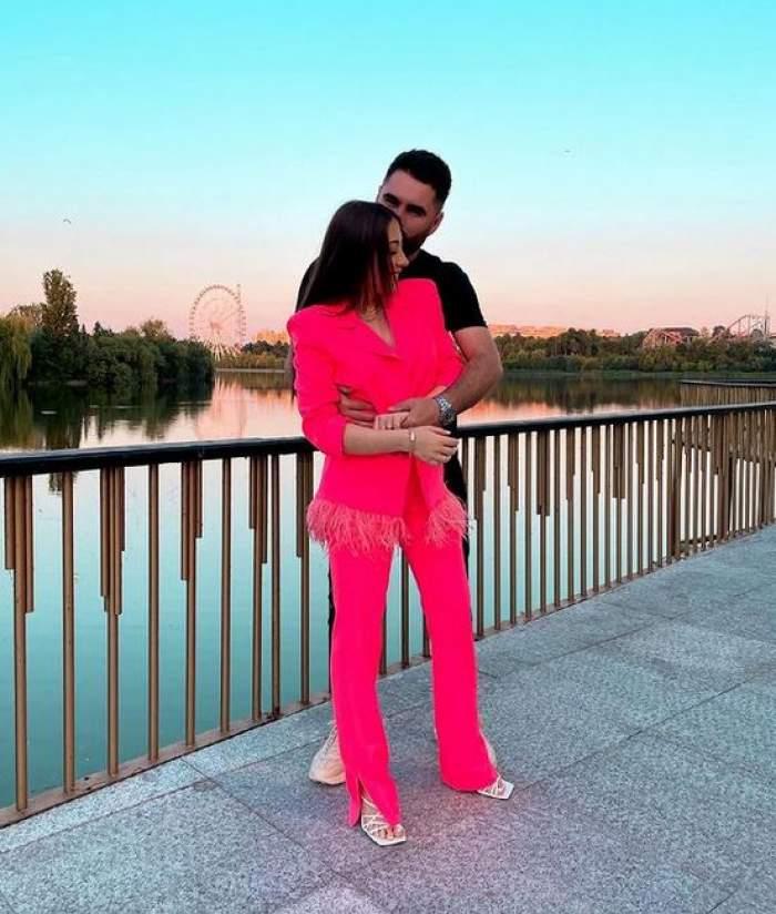 Nicole Cherry și iubitul ei sunt lângă un lac. Vedeta poartă costum roz și e ținută în brațe pe la spate de el.