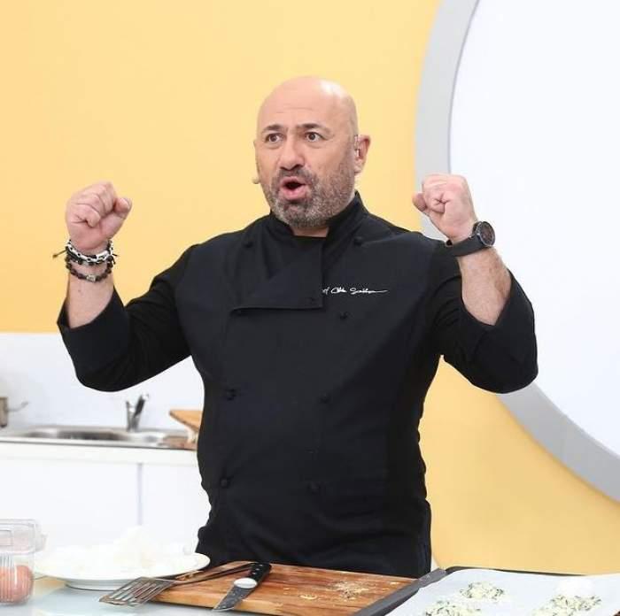 Cătălin Scărlătescu poartă o uniformă de bucătar neagră. Chef-ul e în bucătăria de la Chefi la cuțite și ține pumnii ridicați în aer, având gura deschisă.