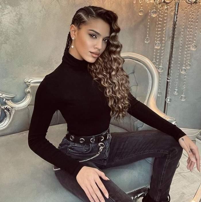 Karmen Simionescu stă pe canapea gri și e îmbrăcată în negru.