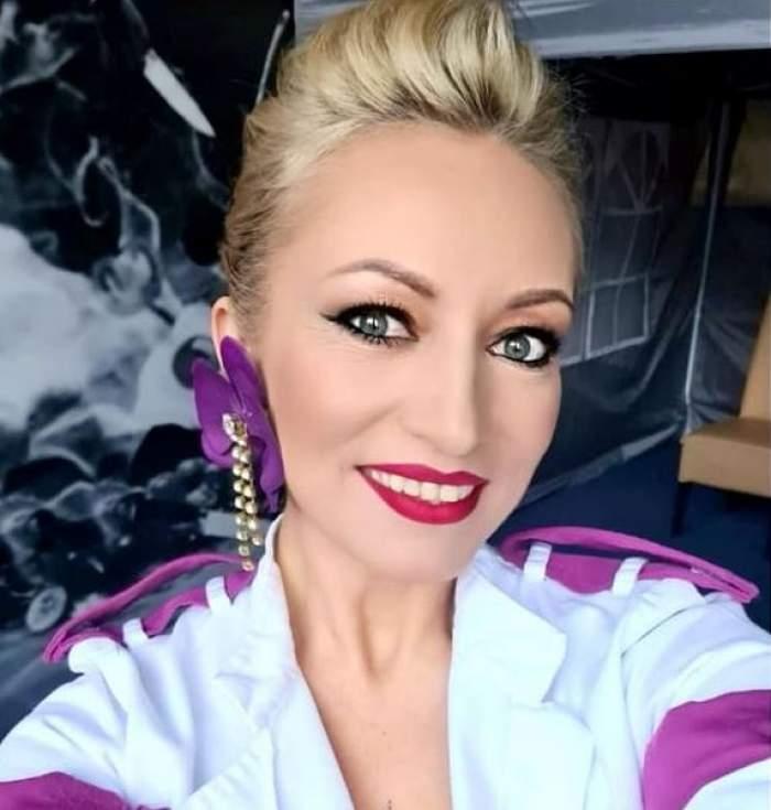 Nicoleta Pop își face un selfie în care zâmbește și poartă uniformă albă de bucătar cu nuanțe de mov.