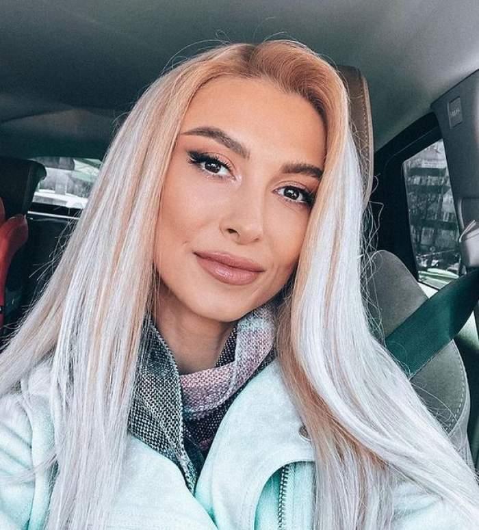 Andreea Bălan e în mașină și zâmbește discret. Vedeta poartă o geacă bleu deschis spre alb și eșarfă colorată.