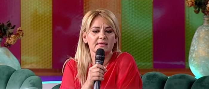 Nicola e la Antena Stars, vorbește la microfon și poartă o bluză roșie.