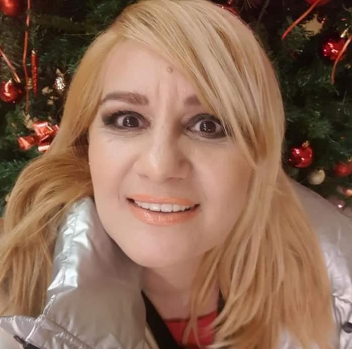 Nicola e îmbrăcată cu o geacă argintie, își face un selfie și zâmbește larg. E dată cu ruj oranj pe buze.