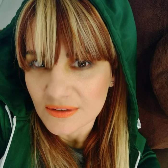 Nicola își face un selfie și poartă hanorac verde, având gluga pe cap.