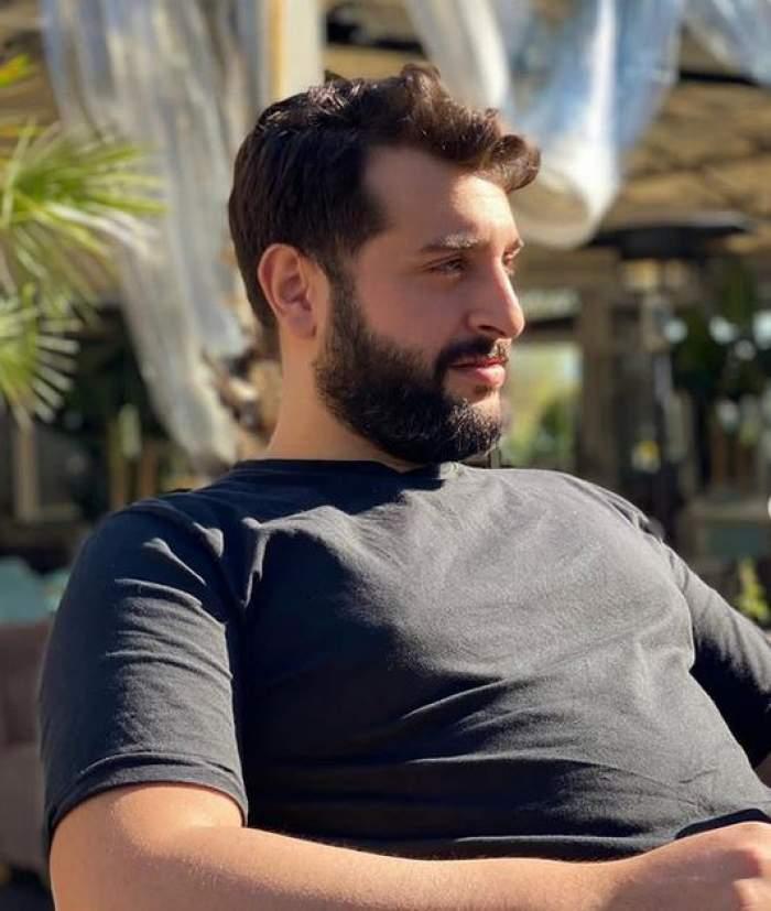 Enzo de la Chefi la cuțite stă pe scaun la terasă și poartă un tricou negru.