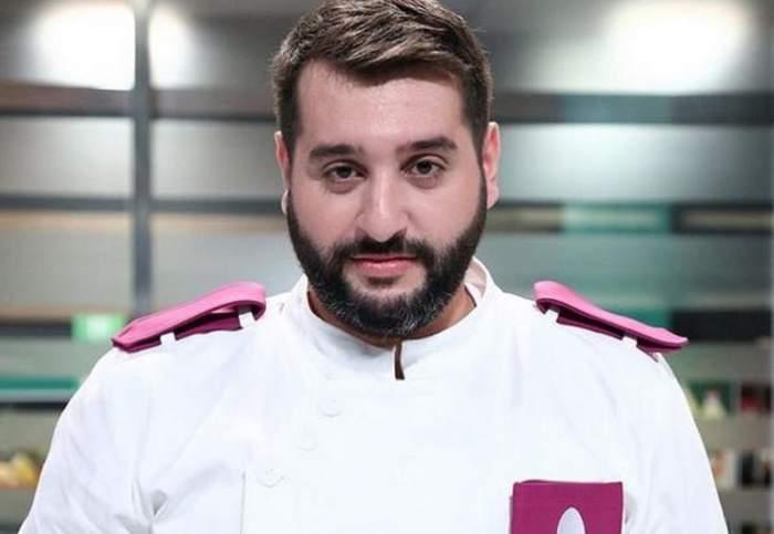 Enzo de la Chefi la cuțite poartă uniformă albă de bucătar cu detalii mov. Acesta zâmbește discret.