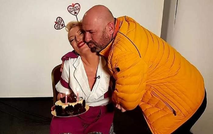 Nicoleta Pop stă pe scaun ținând un tort în mână și e îmbrățișată de Cătălin Scărlătescu care poartă o geacă galbenă.