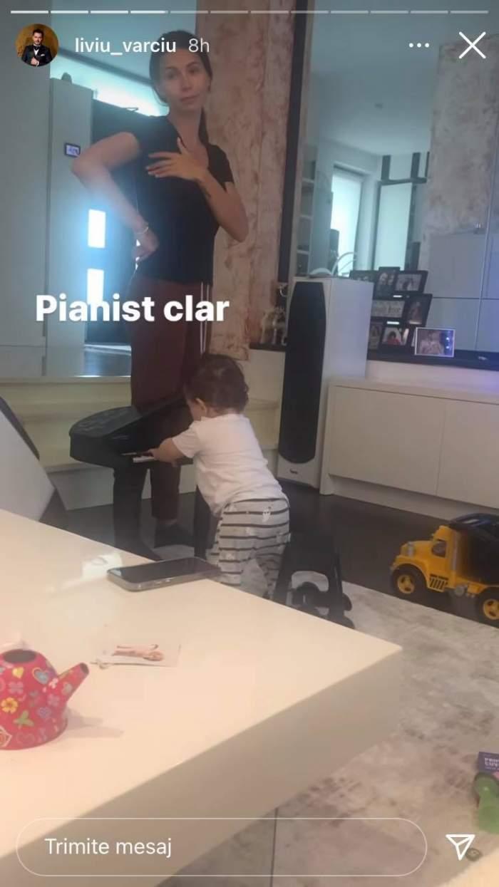 Anda Călin și fiul ei sunt în sufragerie. Micuțul cântă la pian, iar mama lui e îmbrăcată cu tricou negru.