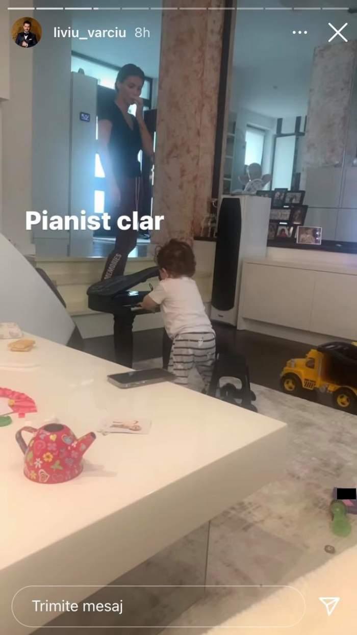 Fiul lui Liviu Vârciu stă în picioare și cântă la pian. Micuțul poartă pantaloni în dungi, tricou alb și e supravegheat de Anda Călin, mama lui.