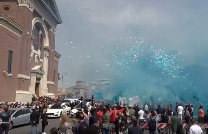 O imagine de la înmormântarea lui Daniel și David Fusinato, frățiorii omorâți într-un parc din Italia. Oamenii au eliberat fumigene albastre și albe.