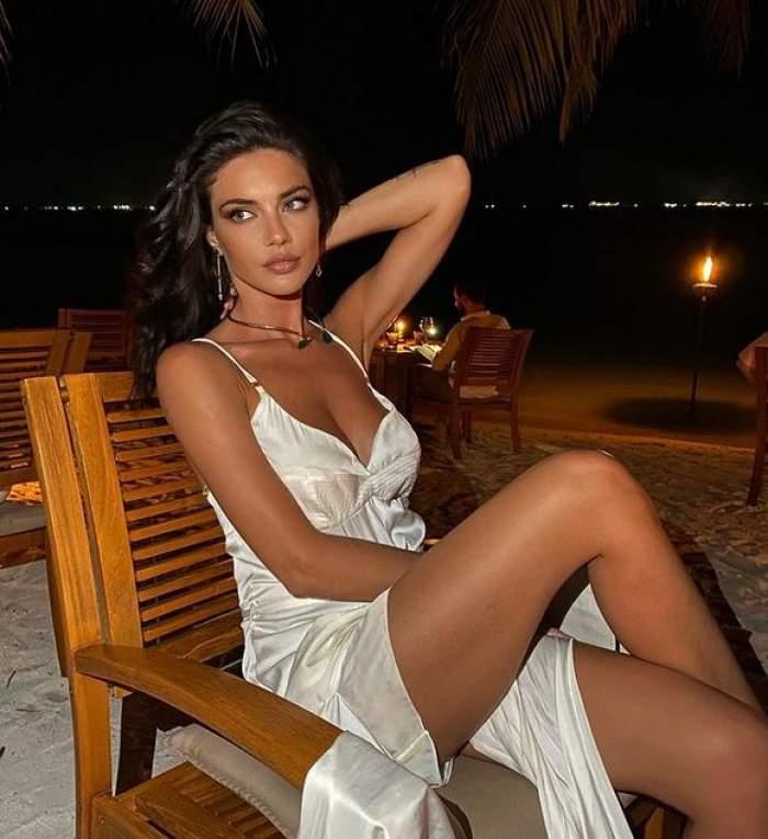 Cristina Ich stă pe un scaun din lemn, pe plajă, și poartă o rochie albă.