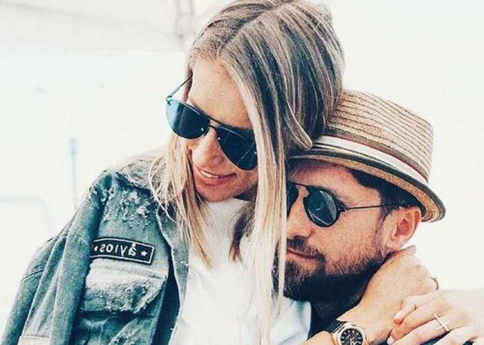 Gabriela Prisăcariu și Dani Oțil se țin în brațe. Ea poartă bluză albă, ochelari de soare și geacă de blugi, iar el ochelari de soare și pălărie crem.