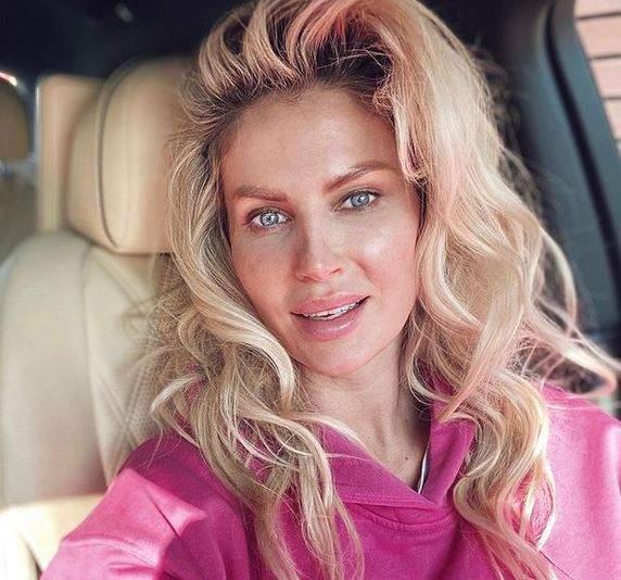 Andreea Bănică e în mașină. Vedeta e nemachiată și poartă un hanorac roz.