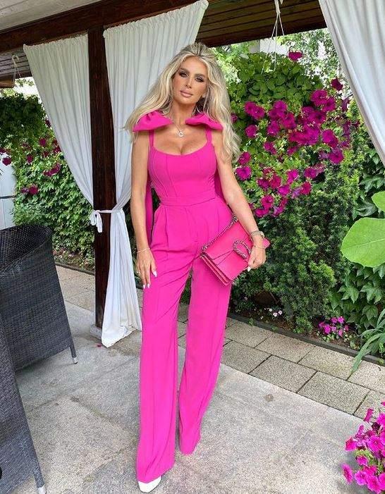 Andreea Bănică e pe terasă, poartă pantofi albi, salopetă roz și ține în mână o geantă roz.