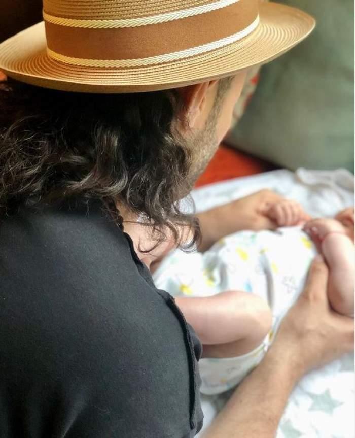 Smiley ține mâinile pe fiica lui, Josephine. Artistul poartă pălărie crem și tricou negru.