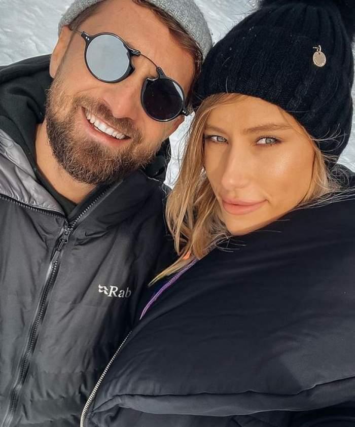 Gabriela Prisăcariu și Dani Oțil sunt la munte. Ea poartă căciulă neagră și geacă neagră, iar el căciulă gri și ochelari de soare.