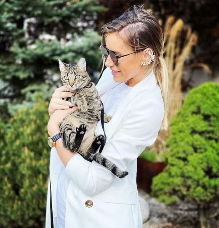 Gabriela Prisăcariu poartă un sacou alb, are părul prins și o ține în brațe pe pisica ei. Vedeta e afară.