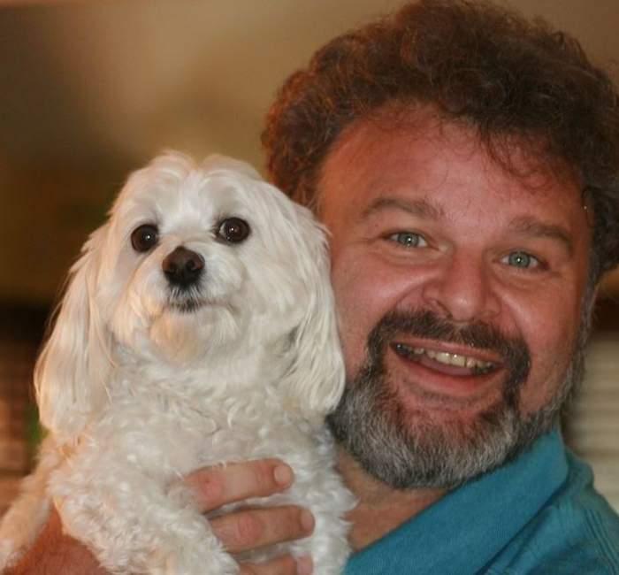 Tudor Petruț zâmbește și poartă un tricou bleu. Actorul își ține în brațe câinele alb.