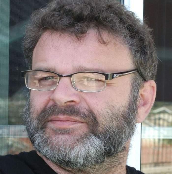 Tudor Petruț poartă ochelari de vedere, tricou negru și privește într-o parte.