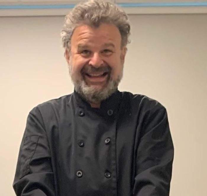 Tudor Petruț poartă o uniformă neagră de bucătar și zâmbește larg.
