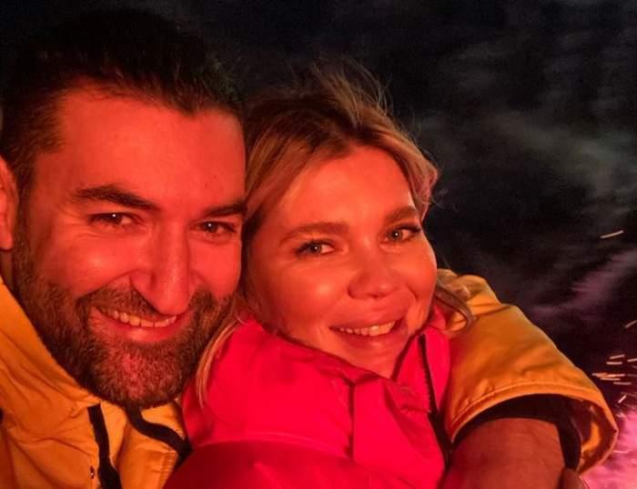 Smiley și Gina Pistol își fac un selfie. El poartă o geacă galbenă, iar ea una roșie. Amândoi zâmbesc larg.