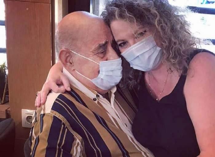 Oana și Viorel Lis se țin în brațe. Cei doi poartă mască de protecție. Ea e îmbrăcată cu un maiou negru, iar el cu un tricou în dungi.