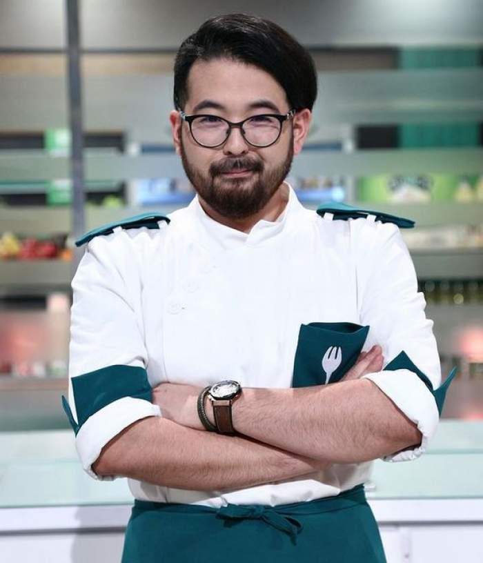 Rikito Watanabe e la Chefi la cuțite și poartă uniformă albă cu verde, ochelari de vedere și își ține mâinile-n sân.