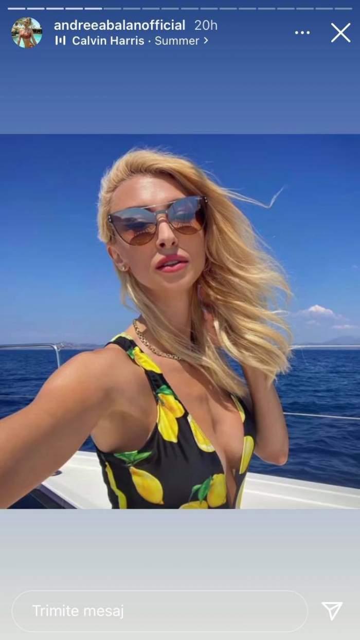 Andreea Bălan se află pe vapor, în Grecia. Artista poartă ochelari de soare și costum de baie negru cu model cu lămâi.