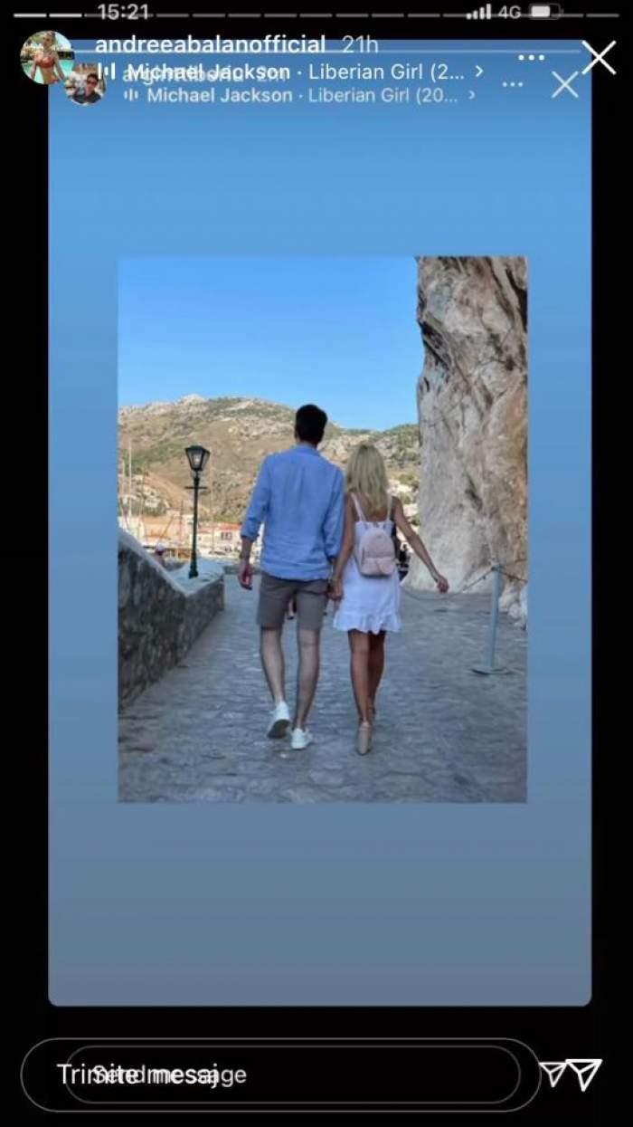 Andreea Bălan și Tiberiu Argint se plimbă de mână pe străzile din Grecia. Artista poartă sandale cu toc, rochie albă și rucsac în spate, iar el pantaloni gri și cămașă bleu.