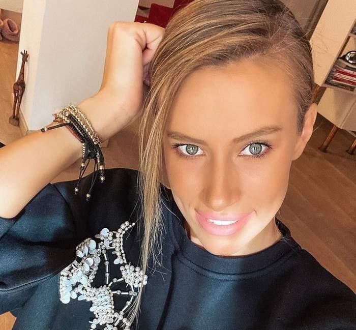 Gabriela Prisăcariu își face un selfie. Vedeta poartă o bluză neagră cu un model cu paiete albe și zâmbește.