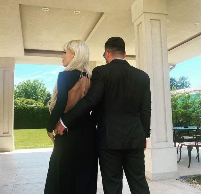 Bianca Rus și noul iubit se află afară și stau cu spatele la cameră. Ea poartă rochie neagră, iar el costum negru și o ține în brațe cu o mână.
