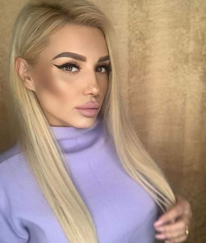 Bianca Rus poartă un pulover mov, are o mână prin păr și părul dat după ureche.