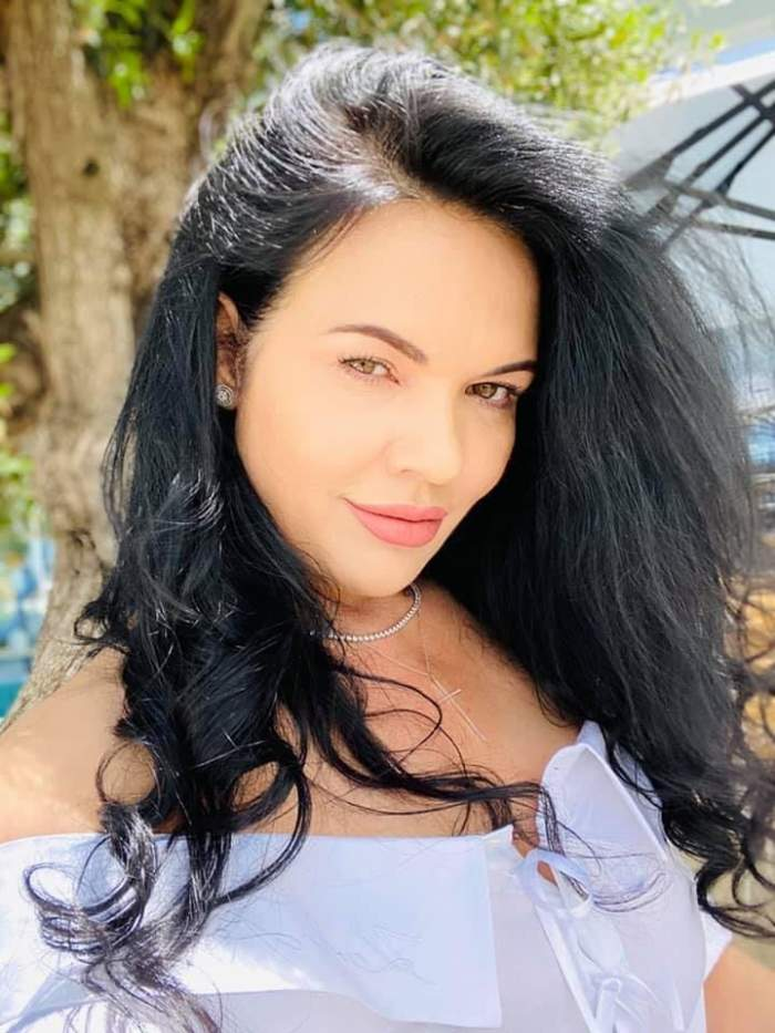 Ioana Simion își face un selfie, poartă cămașă albă și zâmbește slab.