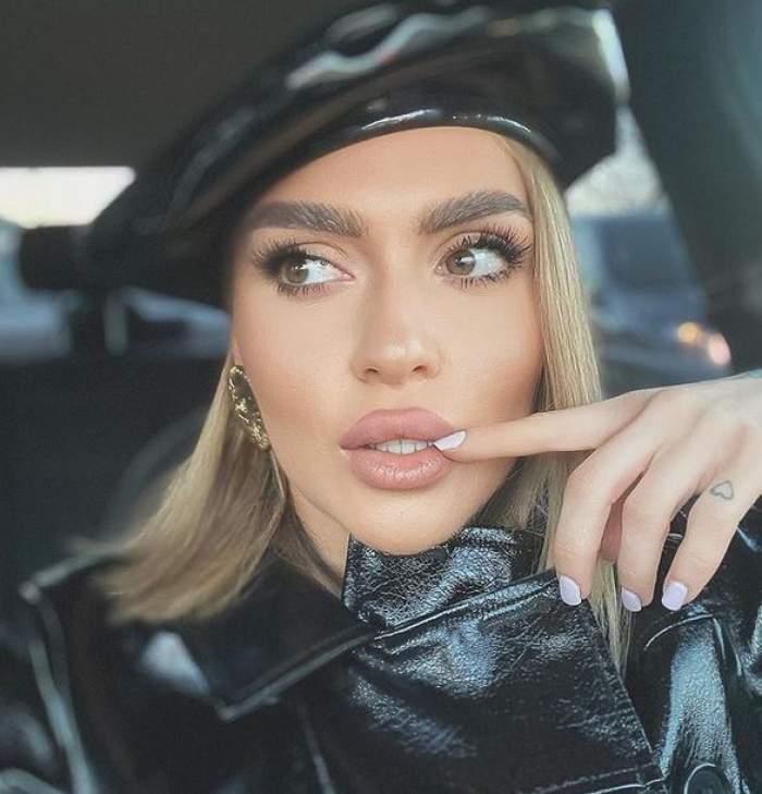 Oana Radu se află în mașină. Vedeta poartă o beretă și o haină neagră, din piele. Artista își ține un deget la nivelul buzelor.