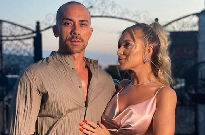 Oana Radu și soțul ei se află la un eveniment. Ea poartă rochie roz și îi ține mâna pe piept, iar el poartă cămașă crem.