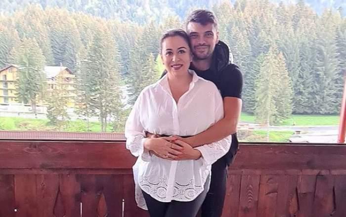 Oana Roman și Marius Elisei sunt la munte. El o ține în brațe pe la spate, iar ea își ține mâinile pe ale lui. Vedeta poartă cămașă albă.
