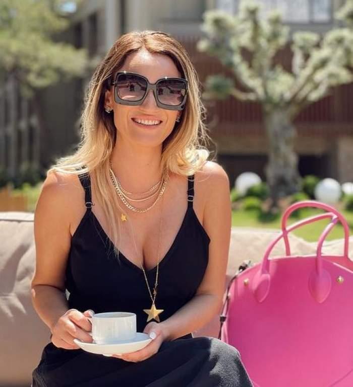 Carmen Neogiță e la terasă, ține o ceașcă albă de cafea în mână și poartă ochelari de soare și rochie neagră.