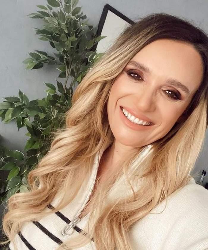 Carmen Neogiță își face un selfie în care zâmbește larg și are părul aranjat în bucle lejere.