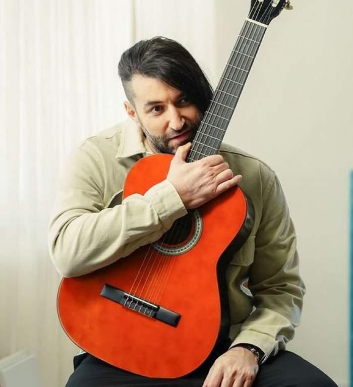 Smiley stă pe un scaun, cu chitara lui în brațe. Artistul poartă pantaloni negri și cămașă verzuie.