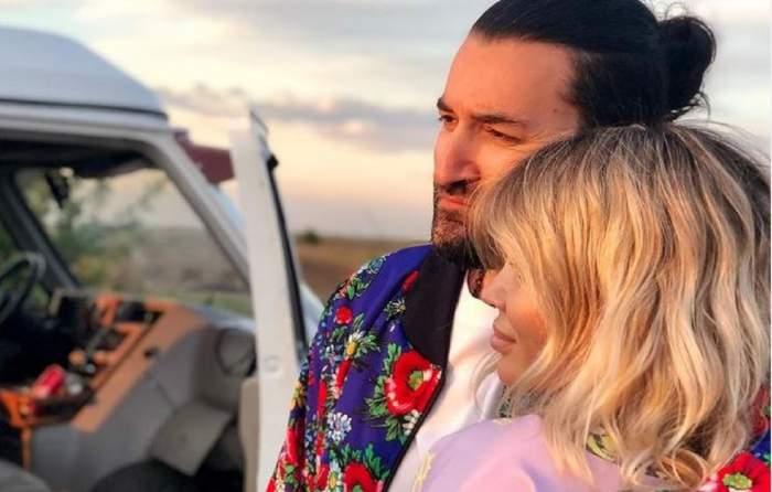 Smiley și Gina Pistol sunt pe un câmp. El o ține în brațe, are părul prins și poartă o jachetă colorată.