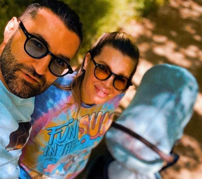 Smiley și Gina Pistol într-un selfie. Amândoi zâmbesc și poartă ochelari de soare. Lângă ei este căruciorul de copii bleu al fiicei lor, Josephine.