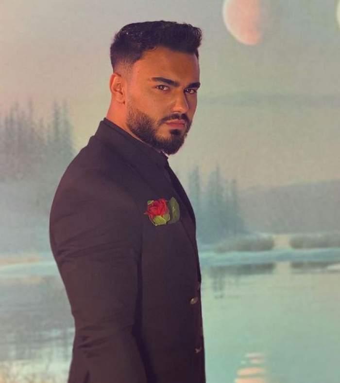 Jador poartă sacou negru și are în buzunar un trandafir roșu.