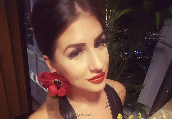 Alexandra Diaconescu într-un selfie. Vedeta are părul prins și poartă o rochie neagră și are un cercel în formă de floare roșie.