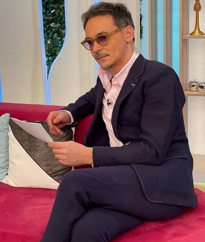 """Răzvan Simion stă pe canapea, în platoul emisiunii """"Neatza cu Răzvan Și Dani"""". Prezentatorul stă picior peste picior și poartă un costum bleumarin, pe dedesubt având o cămașă albă."""