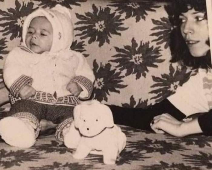 Răzvan Simion în copilărie alături de mama lui. Cei doi stau pe canapea și ea îi susține spatele cu mâna.