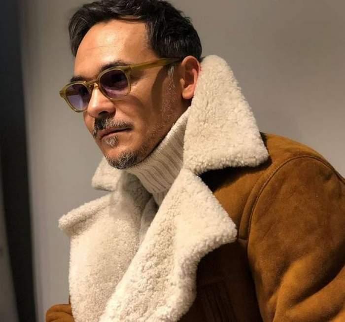 Răzvan Simion poartă o geacă maro cu guler crem, iar pe dedesubt un pulover bej. Prezentatorul poartă ochelari de vedere cu lentine închise la culoare.