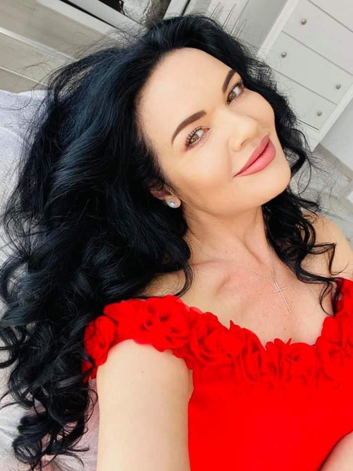 Ioana Simion poartă o bluză roșie cu motive florale și are părul aranjat în bucle.