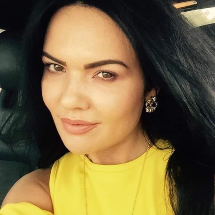 Ioana Simion poartă o bluză galbenă și zâmbește slab făcându-și un selfie.